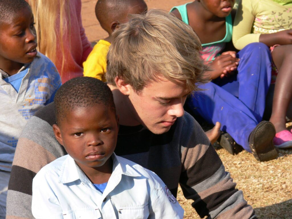 Young man short-term missionary sitting with young boy at host site