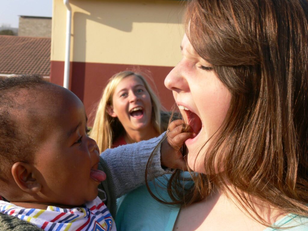 Young woman on short-term missions trip interacting humorously with baby