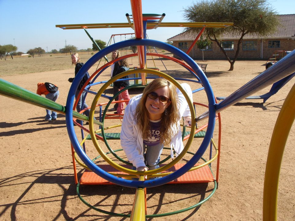 Smiling email trip leader on playground equipment at short-term ministry site