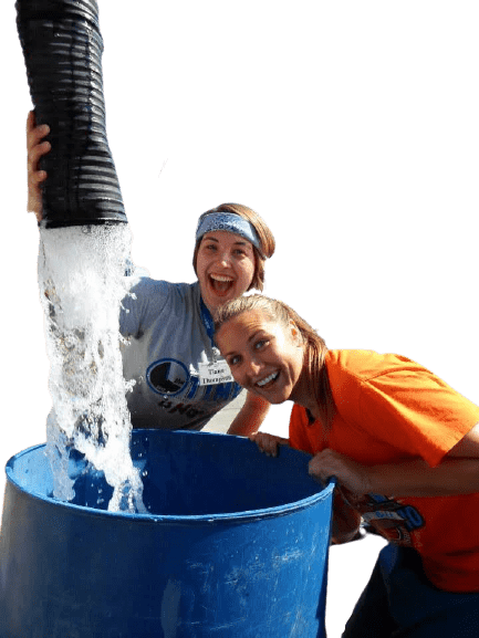 Two young women smile excitedly as water gushes into barrel from large pipe at ministry site