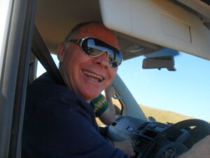 John Jackson smiling with sunglasses while driving left-hand drive van on short-term missions trip in South Africa