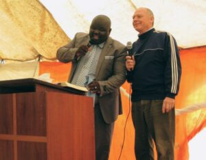 John Jackson preaching with African interpreter in tent